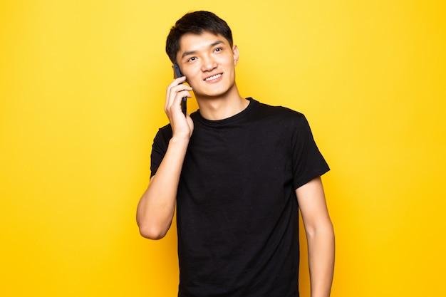 Jovem asiático bonito falar no telefone na parede amarela