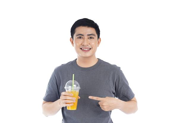 Jovem asiático bonito segurando um copo de plástico de suco de laranja