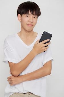 Jovem asiático bonito segurando um telefone celular