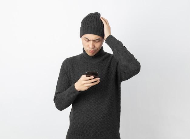 Jovem asiático bonito vestindo gorro e blusa cinza enquanto estiver jogando smartphone com rosto de dúvidas em branco