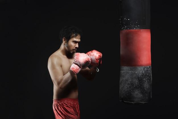 Jovem asiático boxe treino com saco de pancadas