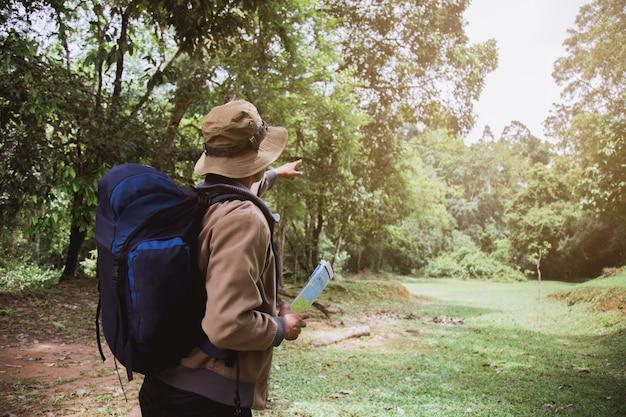 Jovem asiático carregando uma mochila e usando um chapéu