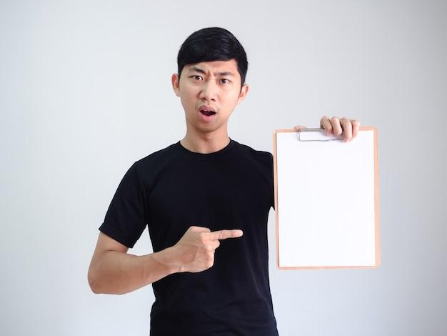 Jovem asiático com camisa preta apontando o dedo para um documento em branco da prancheta de madeira na mão cara séria