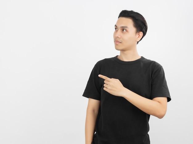 Jovem asiático com camisa preta, apontando para o lado com um dedo para apresentar um produto ou uma ideia enquanto olha para a frente surpreendente isolado no branco