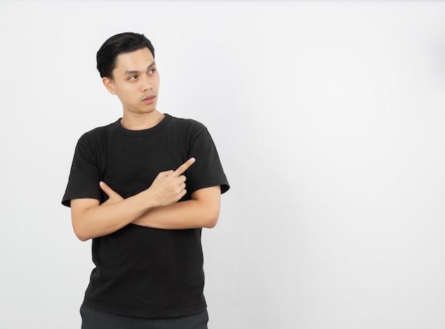 Jovem asiático com camisa preta, apontando para o lado com um dedo para apresentar um produto ou uma ideia enquanto olha para a frente surpreendente isolado