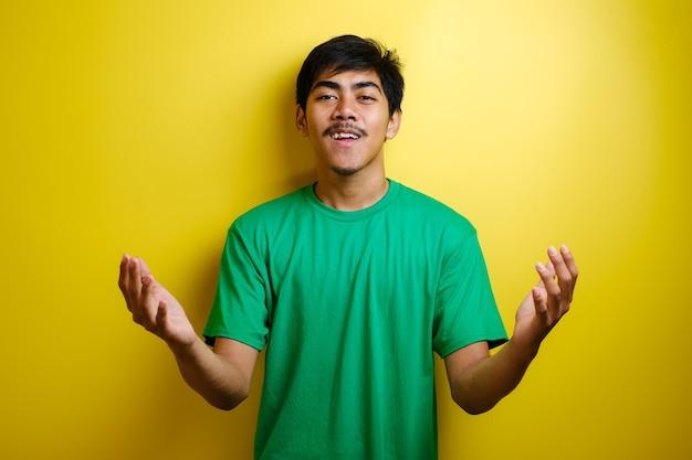 Jovem asiático com camiseta verde sorrindo e mostrando um gesto de boas-vindas contra um fundo amarelo