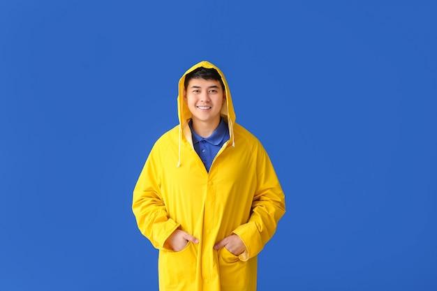 Jovem asiático com capa de chuva na cor de fundo