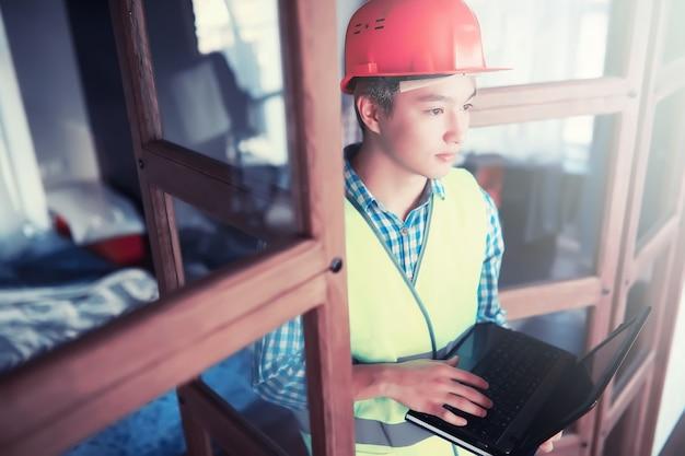Jovem asiático com capacete protetor e colete de construção
