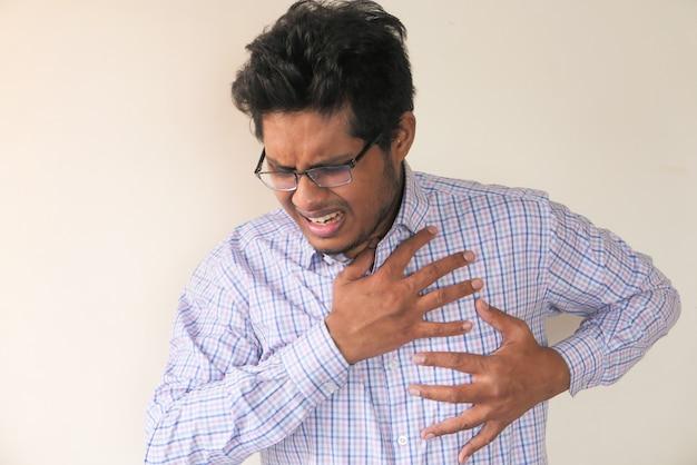 Jovem asiático com dor no coração e segurando o peito com a mão