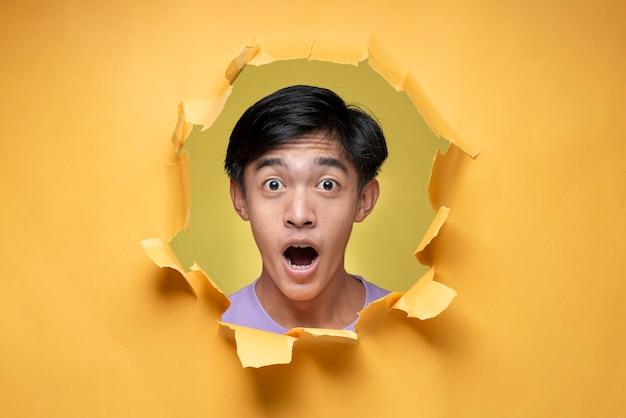 Jovem asiático com expressão chocada e espantada, adolescente, posa através de um buraco de papel amarelo rasgado, vestindo uma camiseta roxa, assustado e chocado com expressão de surpresa, medo e rosto animado