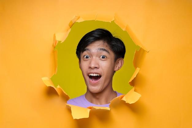 Jovem asiático com expressão de espanto e choque, adolescente, posa através de um buraco de papel amarelo rasgado, vestindo uma camiseta roxa