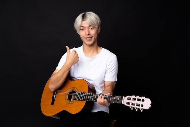 Jovem asiático com guitarra sobre preto com polegares para cima porque algo bom aconteceu