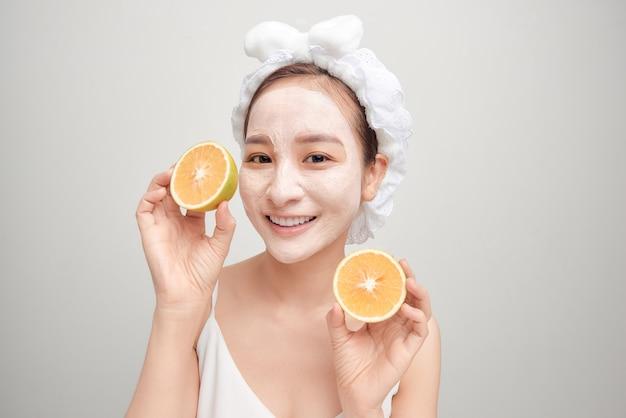 Jovem asiático com máscara de argila facial branca e segurando um pedaço de laranja.