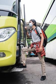 Jovem asiático com máscaras entrando no ônibus. um homem usando máscara e carregando uma mochila entra no ônibus no terminal