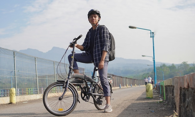 Jovem asiático com mochila descansando depois de andar de bicicleta