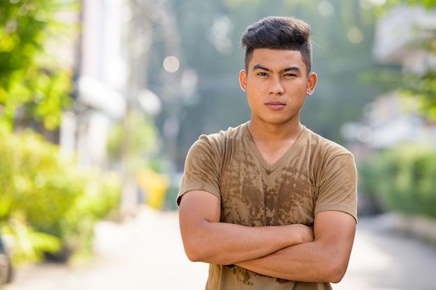 Jovem asiático com os braços cruzados na rua ao ar livre