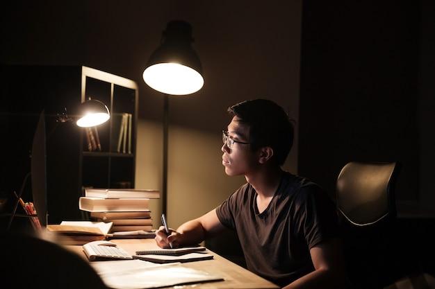 Jovem asiático concentrado de óculos usando o computador para estudar e escrever no bloco de notas à noite em casa