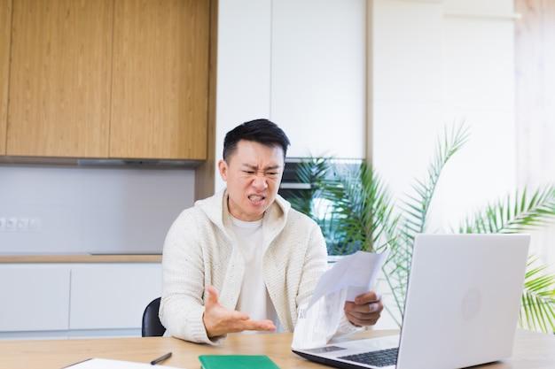 Jovem asiático conta contas, cheques bancários, empréstimos ou serviços públicos, enquanto está sentado em casa na cozinha