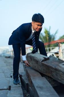 Jovem asiático de terno fazendo esforço ao levantar um tronco