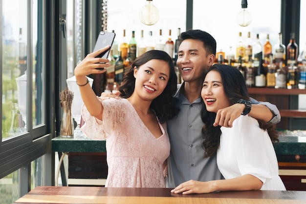 Jovem asiático e duas mulheres abraçando e tomando selfie no smartphone em bar