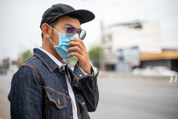 Jovem asiático em pé na cidade e usando máscara de proteção no rosto para proteção da poluição do ar, partículas e proteção contra vírus da gripe, influenza, coronavírus na cidade