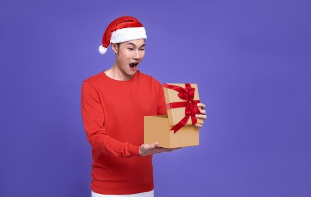 Jovem asiático em traje vermelho casual, usando chapéu de papai noel, abrindo a caixa de presentes e olhando animado e surpresa algo dentro da caixa isolada na parede roxa. conceito de feliz ano novo.