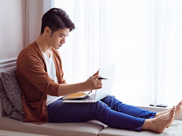 Jovem asiático escrevendo um livro ao usar um laptop