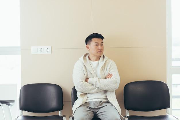 Jovem asiático esperando por uma entrevista ou reunião sentado no corredor na sala de espera. aluno ou participante na recepção para exame ou emprego hr. paciente do sexo masculino no consultório de uma clínica de hospital