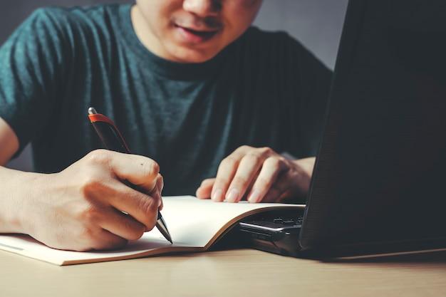 Jovem asiático está escrevendo um livro de lição de casa em uma mesa da casa.