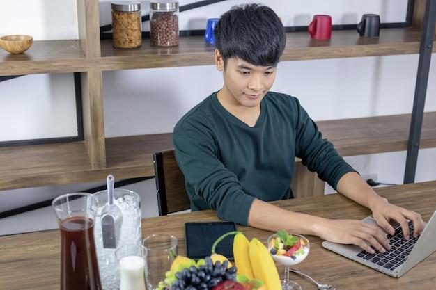 Jovem asiático está sentado em uma moderna sala de jantar
