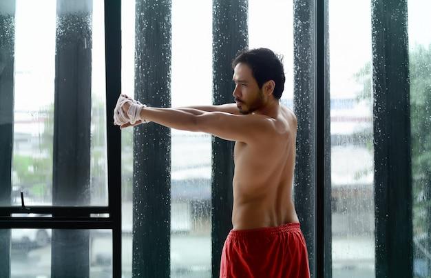 Jovem, asiático, esticar, bíceps