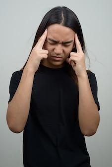 Jovem asiático estressado com cabelo comprido e dor de cabeça