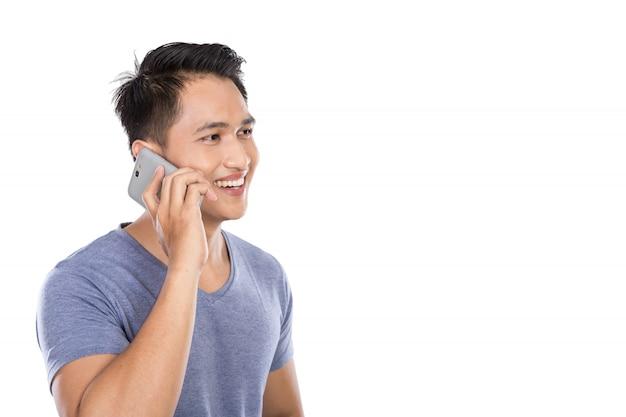 Jovem asiático falando ao telefone isolado na parede branca
