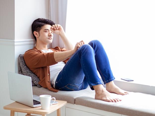 Jovem asiático faz uma pausa após usar o laptop