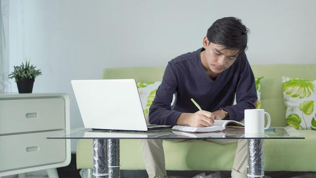 Jovem asiático fazendo anotações sobre o trabalho em casa