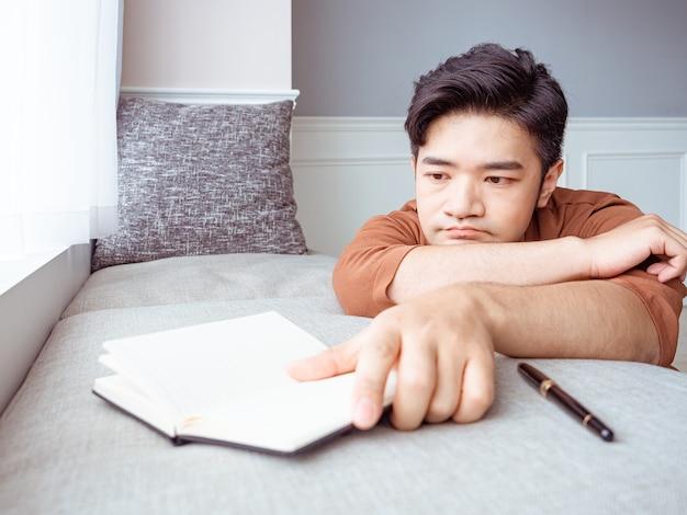 Jovem asiático fazendo uma pausa após ler um livro em casa