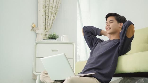 Jovem asiático fechando os olhos pensando em ideias no laptop enquanto está sentado em casa