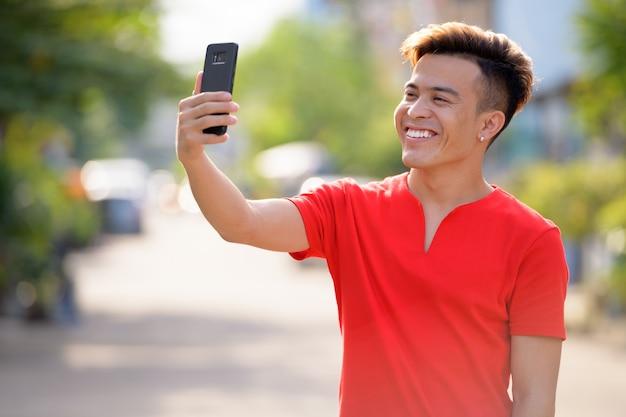 Jovem asiático feliz tirando uma selfie na rua ao ar livre