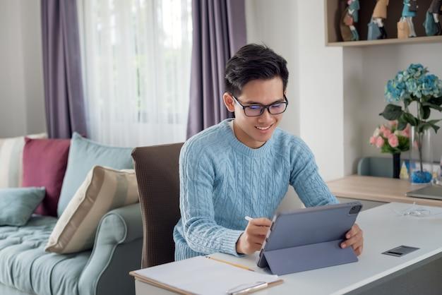 Jovem asiático feliz trabalhando em casa usando um tablet.