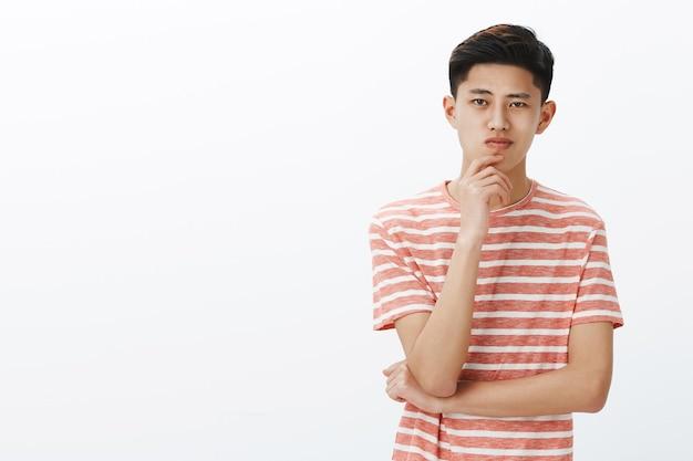 Jovem asiático inteligente e criativo pensando em uma nova invenção. estudante do sexo masculino, chinês atraente, determinado e ambicioso segurando a mão no queixo e sorrindo