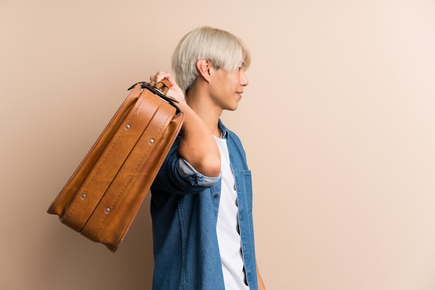 Jovem asiático isolado segurando uma maleta vintage