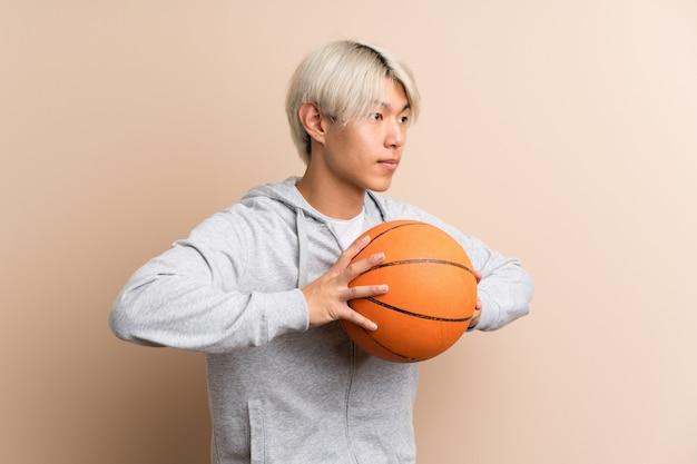 Jovem asiático isolado sobre com bola de basquete