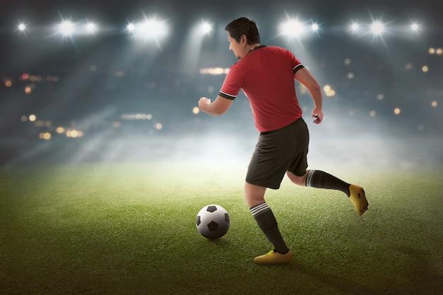 Jovem, asiático, jogador futebol, com, a, bola