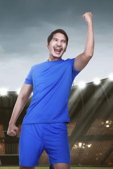Jovem, asiático, jogador futebol, com, excitado, expressão