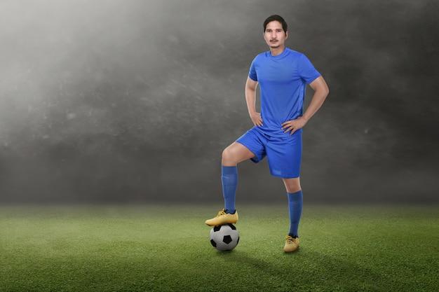 Jovem, asiático, jogador futebol, com, mãos cintura
