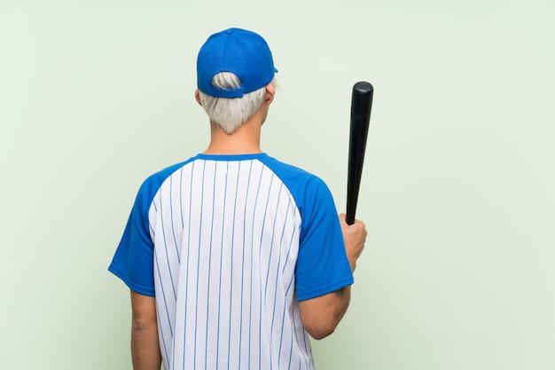 Jovem asiático jogando beisebol na posição traseira
