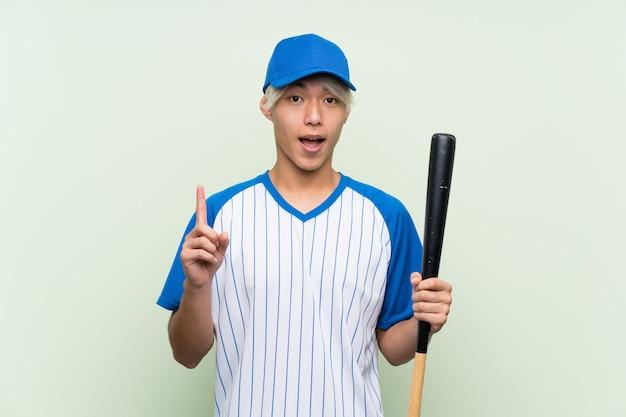 Jovem asiático jogando beisebol sobre verde isolado apontando uma ótima idéia