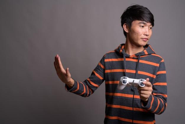 Jovem asiático jogando contra uma parede cinza