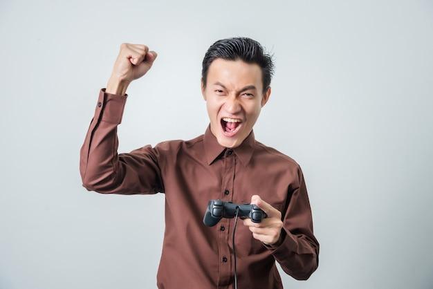Jovem asiático jogando videogame com joystick, sentimento feliz.