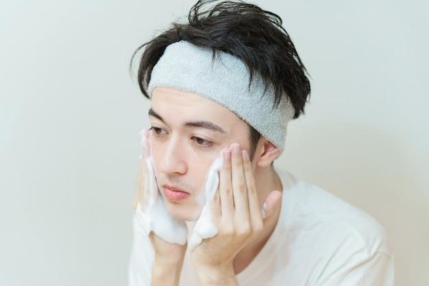 Jovem asiático lavando o rosto